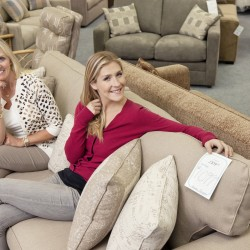 Portrait of happy mother and daughter sitting on sofa in furniture store