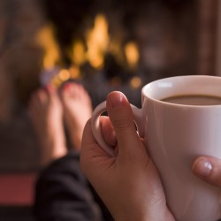 Feet warming at a fireplace with hands holding coffee