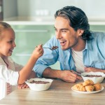 Cute little girl and her handsome father are smiling while having breakfast in kitchen at home. Girl is feeding her dad with a spoon